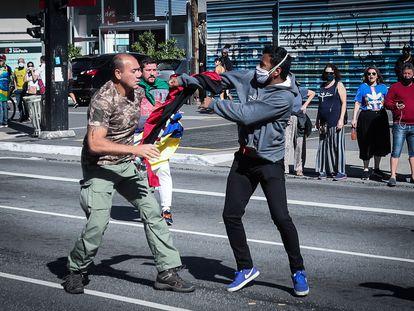 Simpatizante do presidente Bolsonaro segura a bandeira rubro-negra do grupo de extrema-direita ucraniano 'Pravyi Sektor' durante protesto em São Paulo.