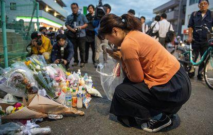 Uma mulher reza diante do local onde um homem atacou um grupo de estudantes com uma faca em Kawasaki, no Japão.