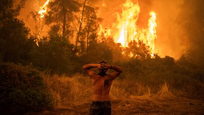 Homem observa um grande incêndio florestal que se aproxima da aldeia de Pefki na ilha de Evia (Eubeia), a segunda maior ilha da Grécia, neste domingo.