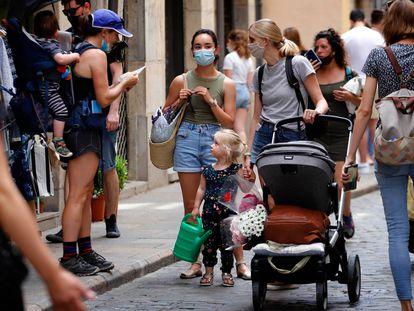 Pessoas passeiam por rua de Girona, na Espanha. O uso de máscara ao ar livre deve deixar de ser obrigatório no próximo dia 26.