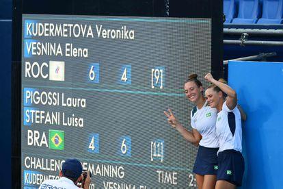 Laura Pigossi (à direita) e Luisa Stefani posam ao lado do quadro de resultados após conquistarem o bronze olímpico inédito.