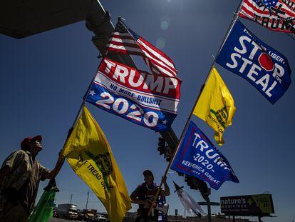Fred F. e Kelly Johnson, seguidores de Trump, protestam nos arredores do centro memorial onde atualmente são apurados os votos da eleição passada em Phoenix (Arizona)