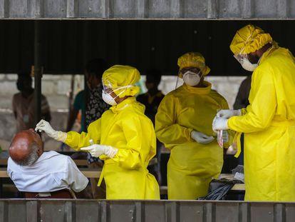 Agentes colhem material para teste de coronavírus no Sri Lanka, nesta quarta.