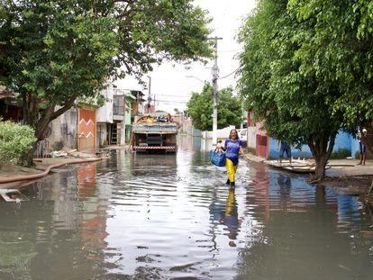 Maria das Graças de Andrade caminha pela rua Tite de Lemos, no Jardim Pantanal, nesta terça-feira. Via estava alagada desde domingo.