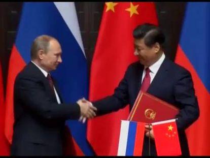 Vladímir Putin da a mão para Xi Jinping, nesta terça-feira em Xangai.