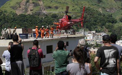 Moradores observam resgate de feridos nos desabamentos na comunidade de Muzema.