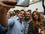 The presidential candidate for Uruguay's Partido Nacional party, Luis Lacalle, takes selfies with supporters after casting his vote at a polling station in Canelones, Canelones Department, during the run-off election on November 24, 2019. (Photo by Pablo PORCIUNCULA BRUNE / AFP)