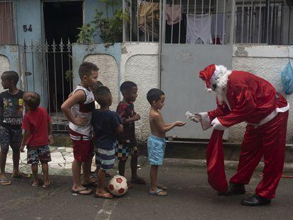 Homem vestido de Papai Noel higieniza as mãos de crianças no complexo de favelas da Maré, Rio de Janeiro, em 23 de dezembro.