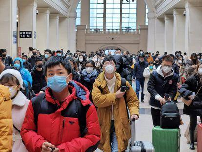Passageiros usam máscaras ao aguardar embarque na estação de trem de Hankou, em Wuhan (China), antes da suspensão do transporte na cidade pelo Governo.