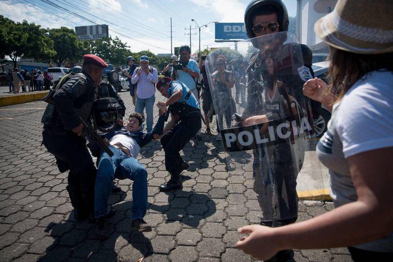 Policiais prendem manifestante na Nicarágua.