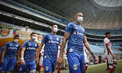 Jogadores do Grêmio entram em campo com máscaras como forma de protesto.