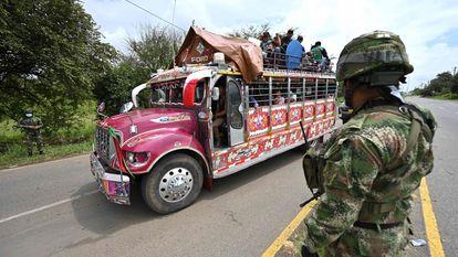 Indígenas colombianos a bordo de um ônibus 'chiva' passam diante de uma tropa militar nos arredores de Cali, na quarta-feira. Em vídeo, a participação dos indígenas nas manifestações.