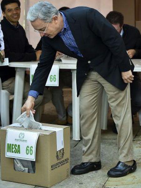 O ex-presidente Álvaro Uribe deposita seu voto na urna.
