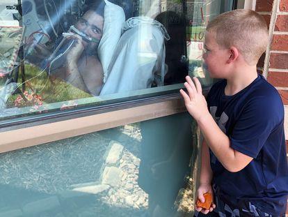 Menino olha para seu pai, nesta quarta-feira, internado por covid-19 em um hospital no Estado de Missouri, EUA.