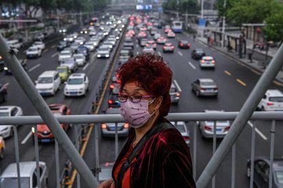 Mulher protegida por máscara cruza por uma passarela em Wuhan, em 14 de maio.