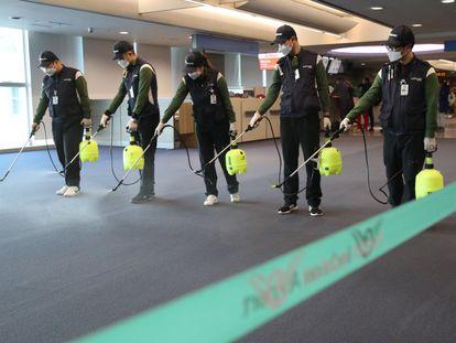 Operários desinfetam a zona alfandegária do aeroporto internacional de Incheon (Coreia do Sul).