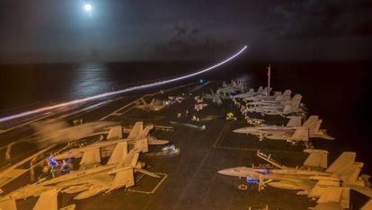 Porta-aviões durante os preparativos para uma missão noturna.