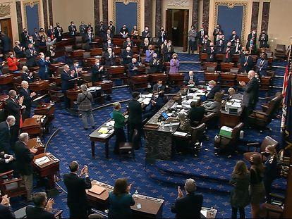 Senadores aplaudem o resultado da votação do plano de resgate, neste sábado, em Washington.
