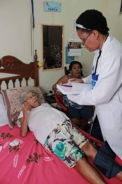 Marlen Cruz Otazo com a paciente Dalila Alves da Silva, em São João de Meriti.