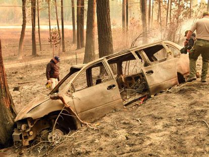 Policiais inspecionam neste domingo um automóvel destruído pelo fogo em Concow (Califórnia).