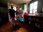 A cabeleireira Jaqueline Silva Viana, de 40 anos, em sua casa, com os filhos Ítalo, 21, e Tamires, 11, e o neto Davi, 3. Desempregada por causa da pandemia, a família depende de doações para viver e já recorreu ao unidades de saúde passando mal de fome. A família mora em Ceilândia, cidade satélite do Distrito Federal, no Brasil.