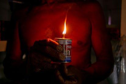 José Silva dos Santos, 55, acende vela em uma latinha de querosene em Provedor II, comunidade de Santana (AP).