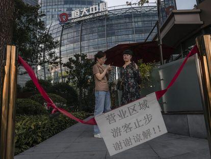 Várias pessoas diante do Centro Evergrande em Xangai, nesta terça-feira.