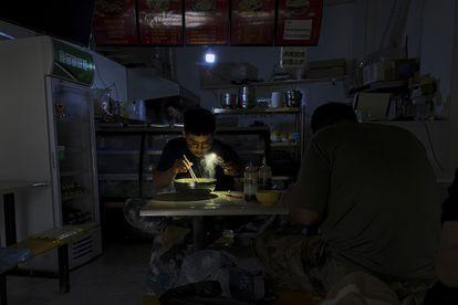 Um homem usa o celular como lanterna enquanto toma o seu café da manhã, durante um blecaute na cidade de Shenyang, no nordeste da China, nesta quarta-feira.
