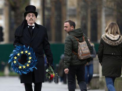 Homem carrega guirlanda em símbolo da União Europeia na praça do Parlamento, em Londres, nesta sexta-feira.