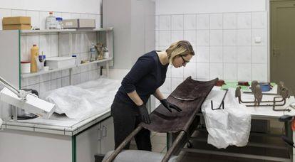Marta Swieton, membro da equipe de restauração, analisa uma maca utilizada no crematório.