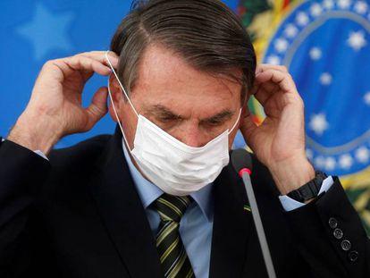 Jair Bolsonaro com uma máscara durante uma entrevista coletiva.