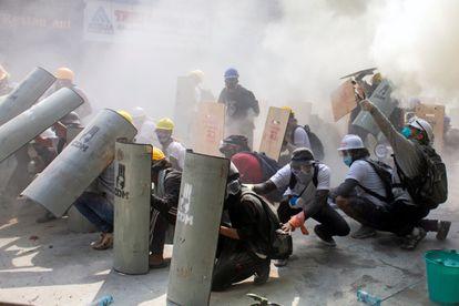 Manifestantes se protegem durante los enfrentamentos com a polícia, em Yangón (Myanmar), este domingo.