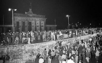 Cidadãos dos dois lados de Berlim celebram sobre o Muro a abertura da fronteira em 9 de novembro de 1989.