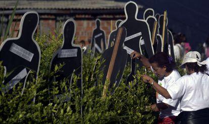 Familiares de desaparecidos em frente às silhuetas com seus nomes.
