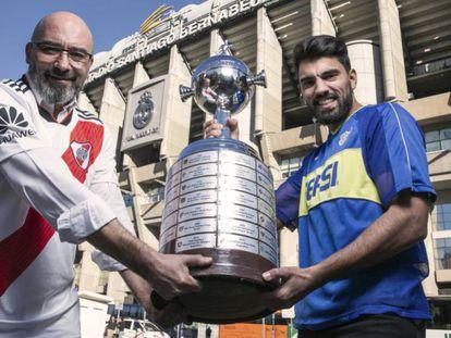 Fabio Vides e Leonardo Polzello, torcedores do River e Boca, posam com uma réplica da Taça Libertadores no Santiago Bernabéu.