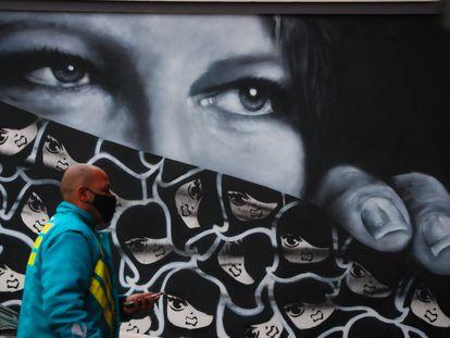 Um homem de máscara caminha com um telefone celular na mão no centro de São Paulo, no último 16 de julho.