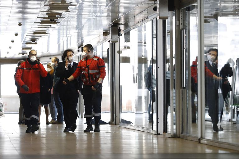 Autoridades com máscaras caminham ao lado de um ônibus da cidade italiana de Milão que ficou em quarentena após a detecção de um caso suspeito de coronavírus.