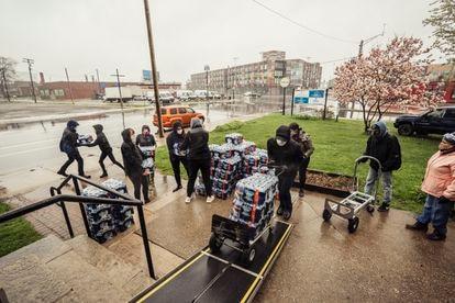 Voluntários de uma empresa local entregam água engarrafada.
