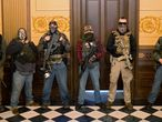 A militia group with no political affiliation from Michigan stands in front of the Governors office after protesters occupied the state capitol building during a vote to approve the extension of Governor Gretchen Whitmer's emergency declaration/stay-at-home order due to the coronavirus disease (COVID-19) outbreak, at the state capitol in Lansing, Michigan, U.S. April 30, 2020.  REUTERS/Seth Herald