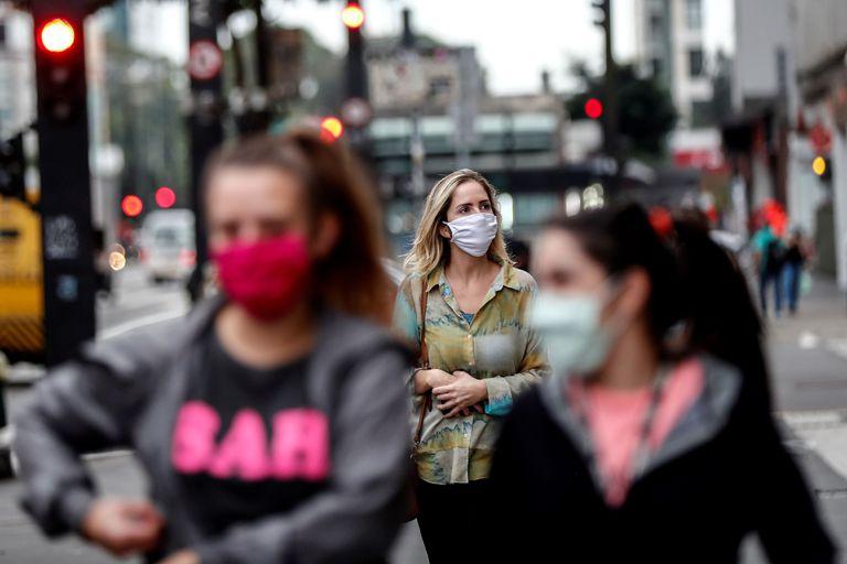 Pessoas com máscaras caminham em São Paulo.