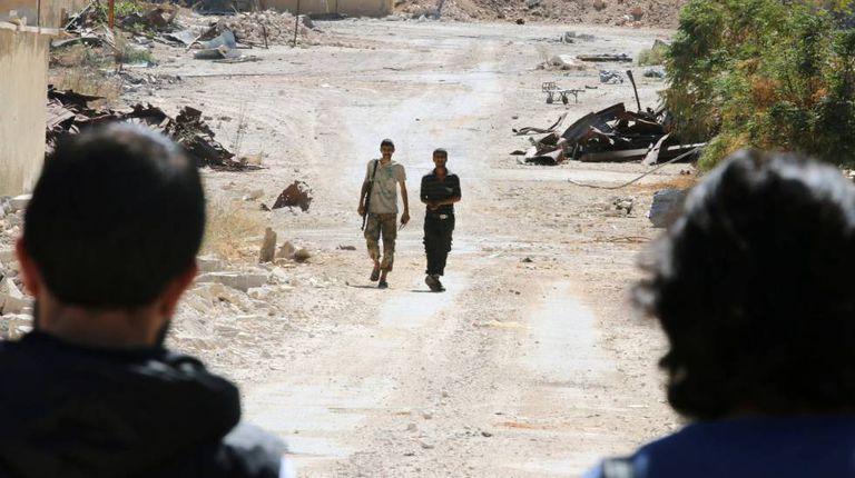 Rebeldes sírios patrulham a principal via de acesso a Alepo.