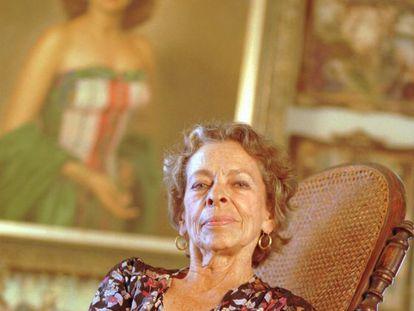 Natalia Revuelta, em sua casa de Havana com seu retrato ao fundo.