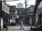 Una calle de Wuhan el pasado 31 de enero. El día antes, el director general de la Organización Mundial de la Salud, declaró la emergencia de salud pública internacional debido al peligro de la expansión del coronavirus.    WUHAN, CHINA - JANUARY 31:  (CHINA OUT) A woman wears a protective mask walk in the street as man sit in the roadside  on January 31, 2020 in Wuhan, China. World Health Organization (WHO) Director-General Tedros Adhanom Ghebreyesus said on January 30 that the novel coronavirus outbreak has become a Public Health Emergency of International Concern (PHEIC).  (Photo by Stringer/Getty Images)