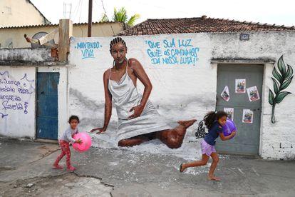 Crianças brincam diante de muro pintado em homenagem a Kathlen de Oliveira Romeu, baleada grávida no Rio de Janeiro no último dia 8.