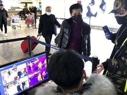 Passageiros passam por controle sanitário no aeroporto de Wuhan, na China.