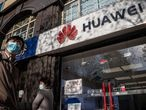 (FILES) In this file photo taken on April 22, 2020, people walk past a Huawei shop in Beijing. - The administration of US President Donald Trump said on May 15, 2020, it would restrict the ability of Chinese telecoms giant Huawei, which it considers a national security risk, to develop semiconductors abroad with US technology. (Photo by NICOLAS ASFOURI / AFP)