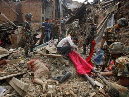 Trabalhadores ao lado de um corpo em Bhaktapur.