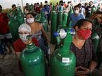 Relatives of patients hospitalised or receiving healthcare at home, who are mostly suffering from the coronavirus disease (COVID-19), gather to buy oxygen and fill cylinders at a private company in Manaus, Brazil January 18, 2021. REUTERS/Bruno Kelly
