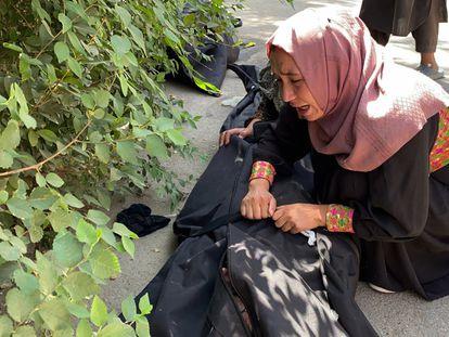 Mulher chora diante de um hospital de Cabul ao lado do corpo de uma vítima do atentado.
