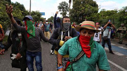 Indígenas caminham por uma rua durante uma manifestação em Cali, neste domingo. Em vídeo, o momento em que um grupo de civis armados se retira após abrir fogo contra a 'minga'.